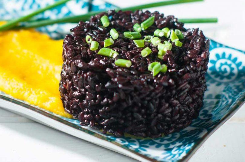 Riso nero venere integrale al profumo di erba cipollina su crema di porri e zafferano